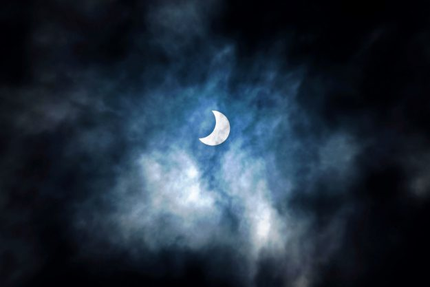 """A picture taken on September 1, 2016 shows the moon moving to cover the sun for a annular solar eclipse in the sky of in Dar es Salaam in Tanzania. Stargazers in south and central Africa are treated to a spectacular solar eclipse on September 1, 2016 when the Moon wanders into view to make the Sun appear as a """"ring of fire"""", astronomers say. The phenomenon, known as an annular solar eclipse, happens when there is a near-perfect alignment of the Earth, Moon and Sun."""