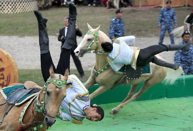 Riders in traditional dress perform stunts on horseback at the opening ceremony of the 2016 World Nomad Games.