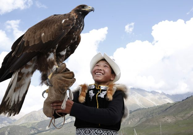 A boy handles an eagle at the World Nomad Games 2016 in Kyrchyn Gorge, Kyrgyzstan.
