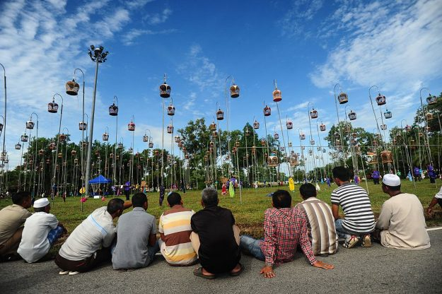 People sit and watch birds hoisted on poled in their cages during a bird-singing contest.