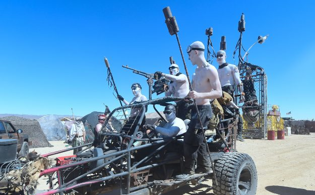 Festival goers replicate the War Boys from Mad Max: Fury Road, complete with wasteland ready vehicle.
