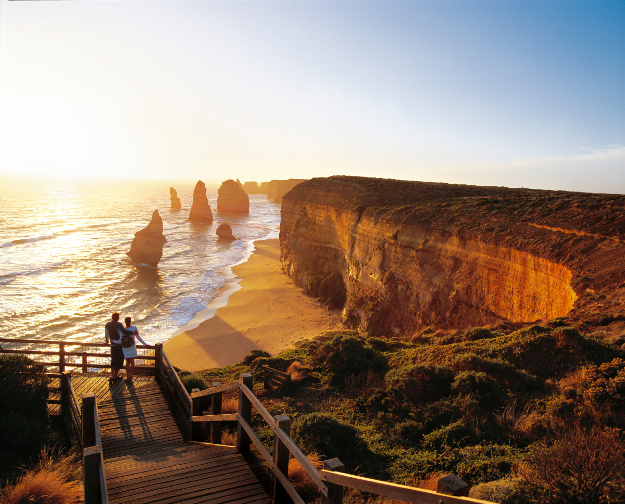 Man and woman admiring the sea at sunset. In the distance are the Twelve Apostles, unique rock formations that rise out of the sea along the Victorian coast.