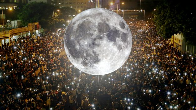 The Moon hangs over an excited crowd as an outside exhibition.