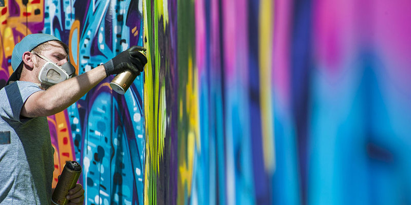 "JOHANNESBURG, SOUTH AFRİCA  - OCTOBER 9: A graffiti artist at work is seen during the 4th annual ""City Of Gold"" Urban Art Festival in Johannesburg South Africa on October 9, 2014. The aim of City Of Gold is to establish Johannesburg as a destination for graffiti and street artists from around the world and assist the development of the local graffiti/street art community.  (Photo by Ihsaan Haffejee / Anadolu Agency / Getty Images)"