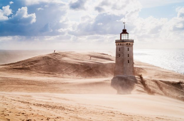 Rubjerg Knude Lighthouse, Northern Jutland in Denmark. Situated on top of a cliff, the lighthouse was built in 1900 and ceased operating in 1968. With coastal erosion and continually shifting sands a major problem in the area, it is anticipated that by 2023 the cliff will have been eroded so far that the lighthouse will fall into the sea.