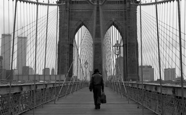 A man walks on a bridge with the Twin Towers on the left side.