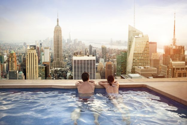 Wonderful Couple Relaxing In Swimming Pool On Hotel Rooftop, Facilities In High End  Hotels