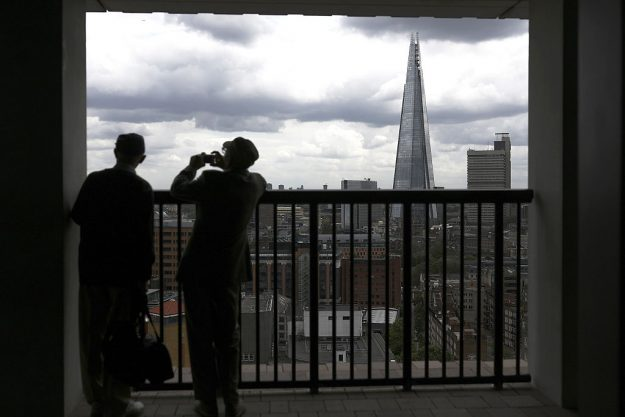 A visitor takes a photograph from the terrace of Switch House, part of the Tate Modern art gallery,