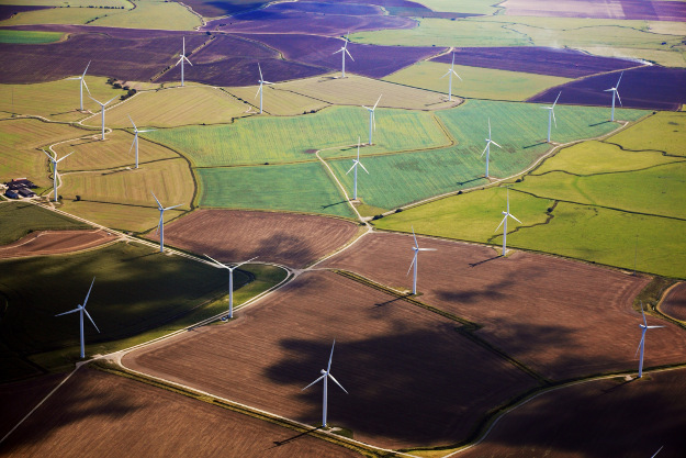 Wind Turbines amidst some colorful fields in Kent viewed from air.