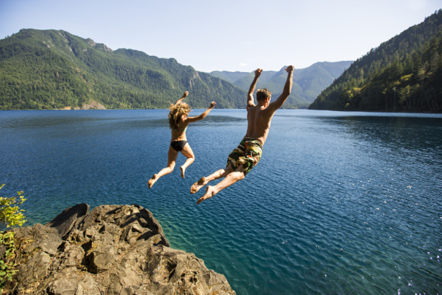 A young couple jumping into a lake in the summer.