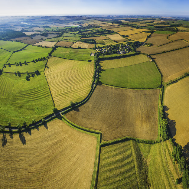 Picturesque patchwork quilt farmland aerial view over fields rural villages in England.