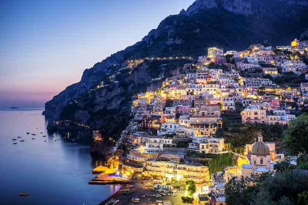 The sun sets over the town of Positano on Italy's Amalfi Coast. We see the boats on the Tyrrhenian Sea and the cliffs in the distance as the lights begin to come on in the town of Positano.