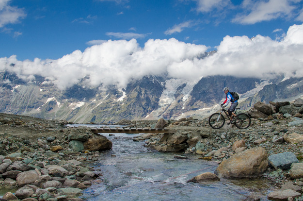 A mountain biker crosses a bridge over a stream with a majestic alpine mountain range in the background.