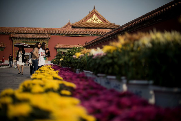 People look at a flower display inside the Forbidden City in Beijing on September 29, 2016. China celebrates 'Golden Week' on October 1 with a week-long holiday to commemorate the founding of the Peoples Republic of China.
