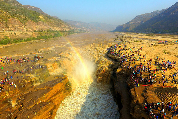 Aerial view of tourists visiting the Hukou Waterfall during the National Day holiday on October 2, 2016 in Yan'an, Shaanxi Province of China. The Hukou Waterfall on the Yellow River attracted thousands of tourists on the second day of the 7-day National Day holiday.