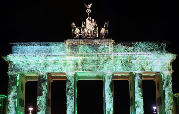 The Brandenburg Gate illuminated with projections.