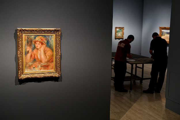 Museum technicians prepare wall labels as Pierre Auguste-Renoir's work 'Young Woman at the Mirror', painted in 1915 and borrowed from the Musee des Beaux-Arts.