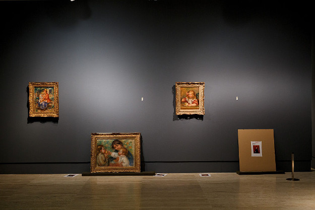 Pierre Auguste-Renoir's work 'Child with an Apple or Gabrielle, Jean Renoir and a Little Girl' (2L) leans on a wall next to other works at the Museum Thyssen-Bornemisza on October 11, 2016 in Madrid, Spain.
