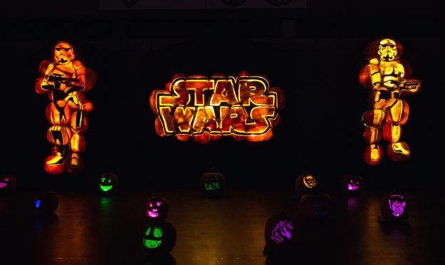 Storm troopers and the Star Wars logo carved out of pumpkins.