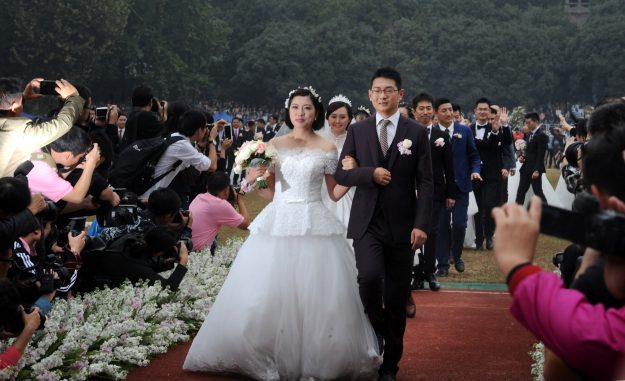 People take photos of couples in a group wedding ceremony on a playground near Science Building at Wuhan University