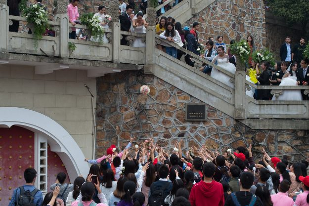 Crowds battle to catch a bouquet thrown at the event.