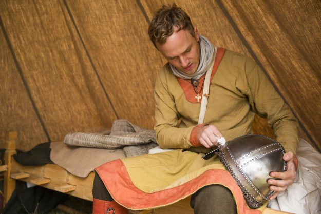 A historical re-enactor in the Norman Camp polishes his helmet before the battle.