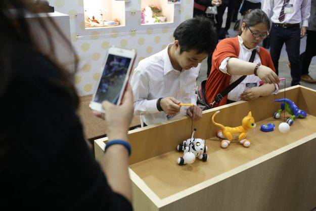 Staff demonstrate the Pet Robots 'Hello! Woonyan' and 'Hello! Zoomer' developed by Takara Tomy.