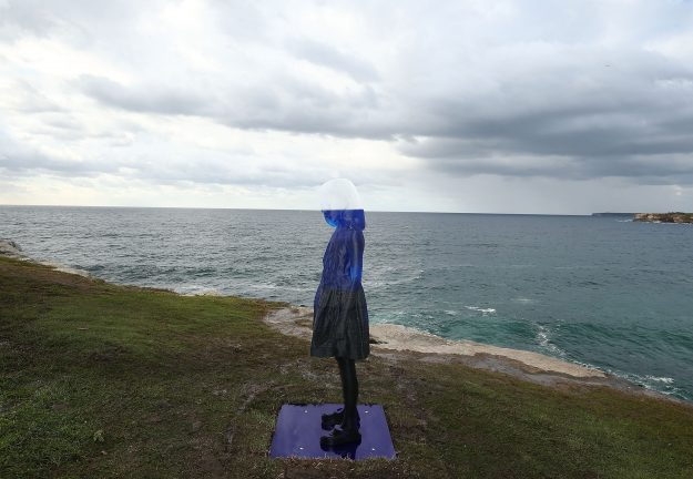 A stunning sculpture of a young girl matching the horizon line at Sculptures by the Sea.