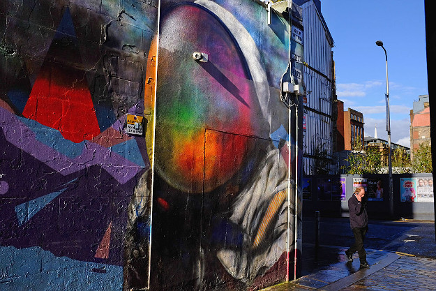Members of the public walk past a mural of a spaceman of Argyll Street.