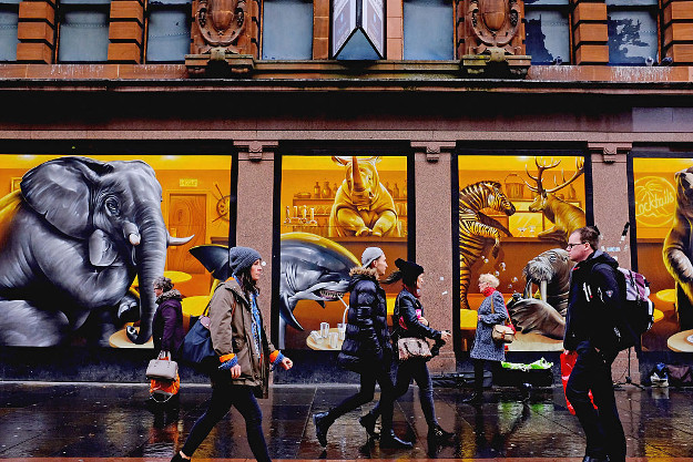 Members of the public walk past amural in Argyll Street.