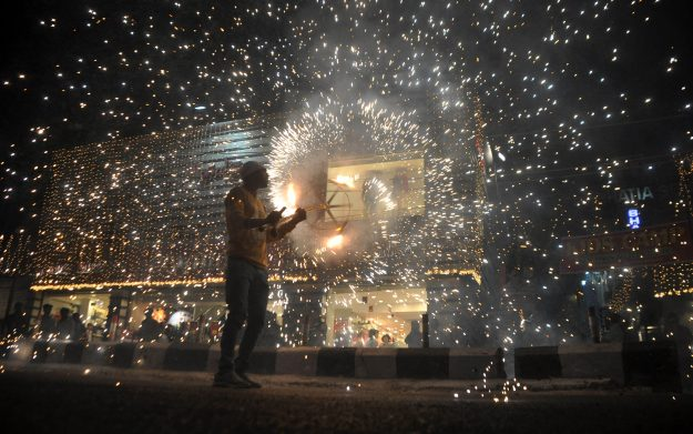 An Indian man sets off firecrackers during a fireworks display at a local marketplace on the eve of Diwali festival in Jammu, India. Image: Stringer/AFP/Getty Images