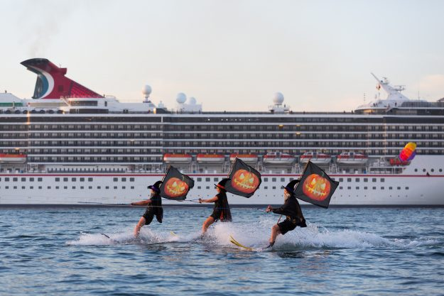 Water skiing witches greet the super liner Carnival Spirit at Sydney Harbour on the eve of Halloween.