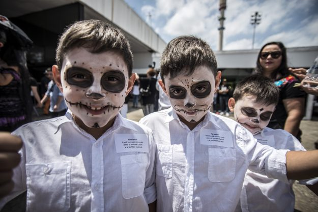 Two children are dressed up as people in costume wait to parade in São Paulo, Brazil.