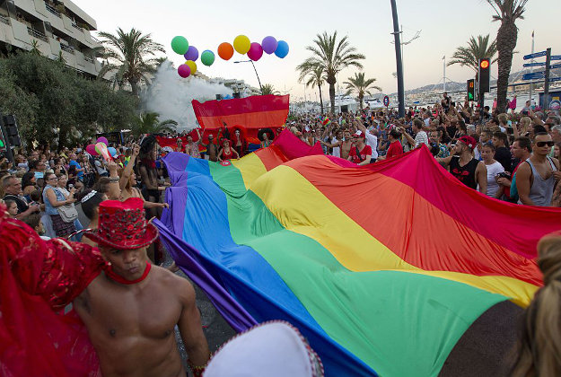 Revelers hold a rainbow flag during the Gay Pride Parade in Ibiza on July 11, 2015