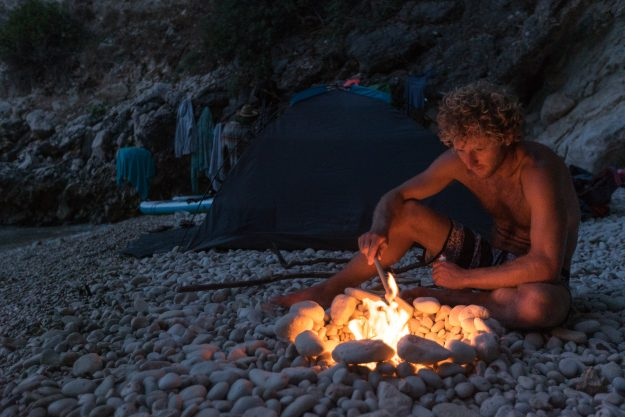 Jay builds a fire on a pebble beach in the evening.
