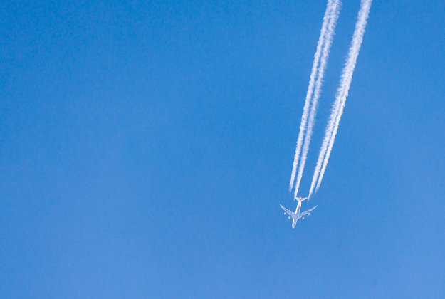 Contrails formed from engine exhaust of aeroplane against clear blue sky.