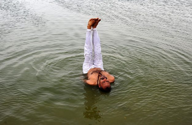 An Indian man performing yoga in Water of River Yamuna