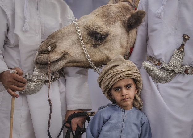 THE BEDOUIN BOY HONORABLE MENTION Author: Habib Alzadjali (OM) Location: Oman Description: A Bedouin boy with his family and their camel. The adults are wearing the traditional Omani Khanjar, a dagger still used in official ceremonies, as well as a symbol of the country.