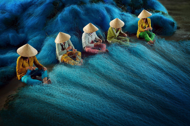 NET MENDING HONORABLE MENTION Author: Hoang Long Ly (VN) Location: Bac Lieu - Vietnam Description: Some Vietnamese women are engaged in carrying out their daily work of mending fishing nets in a fishing village near Bac Lieu, a coastal district located in southern Vietnam, in the Mekong Delta region.