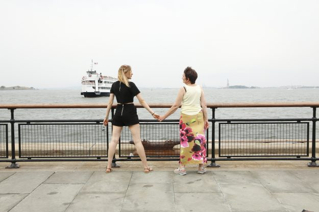 Alex and Halina holding hands in New York with the statue of liberty seen in the background.