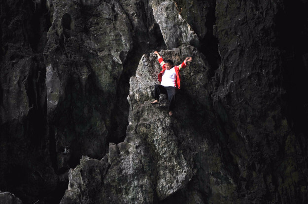 Chinese man Huang Xiaobao of Miao ethnic minority climbs the cliff in a cave at Getu River National Park in Shuitang town.