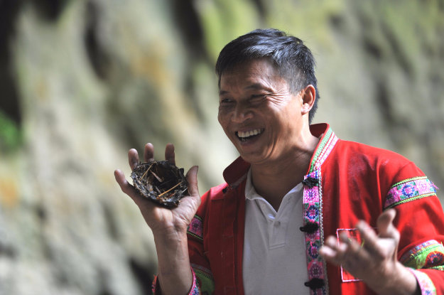 Chinese man Huang Xiaobao of Miao ethnic minority shows a birds nest he found on the cliff in a cave at Getu River National Park in Shuitang town