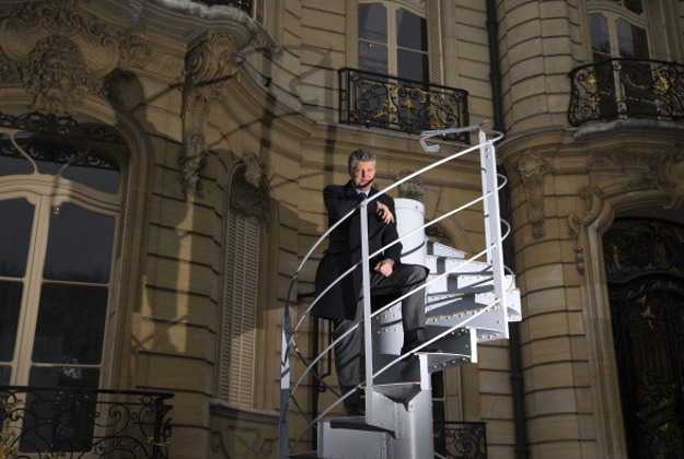 French auctioneer Francois Tajan poses on November 22, 2013 in Paris, in the Artcurial auction yard on a portion of the original staircase of the Eiffel Tower constructed by Gustave Eiffel in 1889.