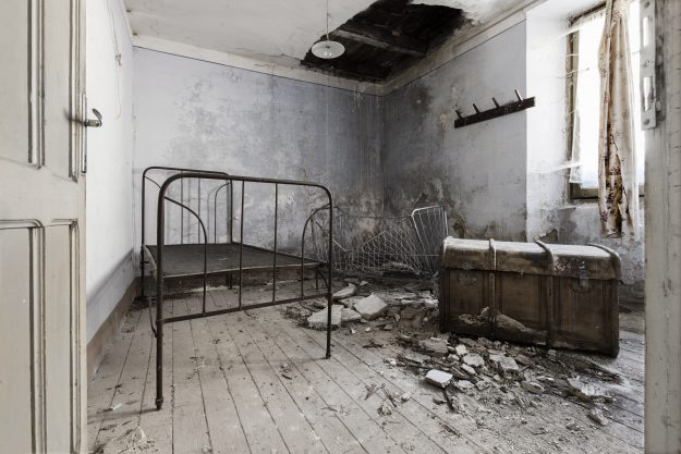 A bare bed frame and an old oversize trunk can be seen in this derelict room.