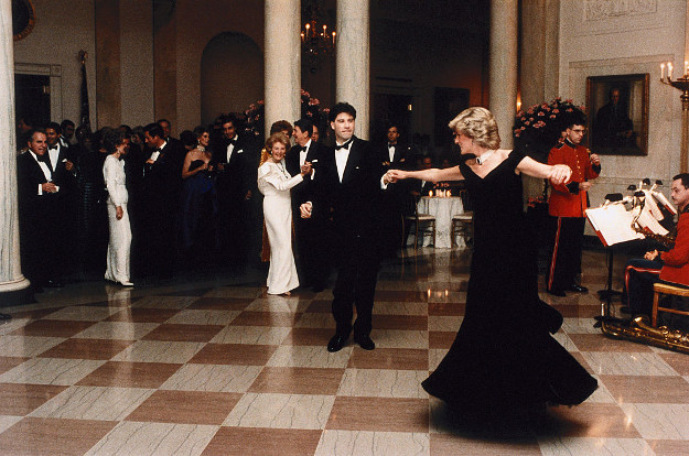 John Travolta twirls Princess Diana on the dance floor while at a White House banquet. Ronald and Nancy Reagan can be seen in the background.