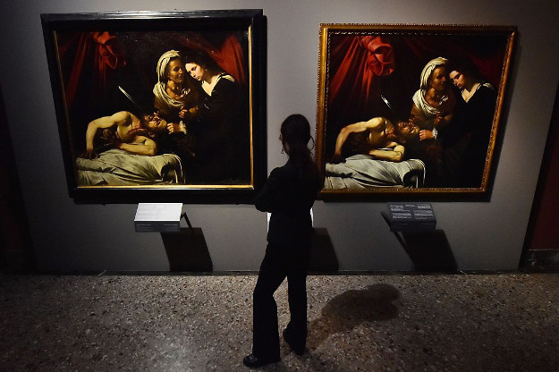 A woman looks at a painting believed to be the 'Judith Beheading Holofernes' by Italian artist Michelangelo Merisi da Caravaggio (L) and a copy of the painting by Flemish artist Louis Finson, on November 9, 2016 at the Brera Art Gallery in Milan.