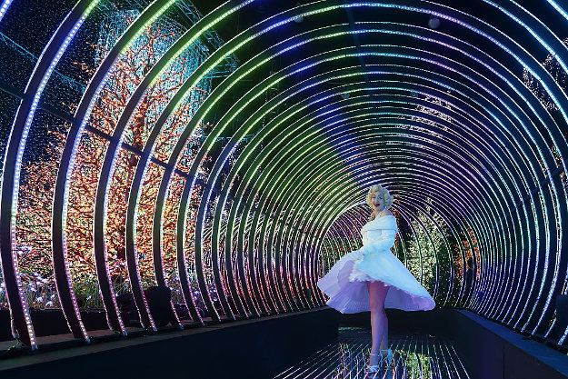 A Marilyn Monroe impersonator poses for a photo inside the Rainbow Connection light display.