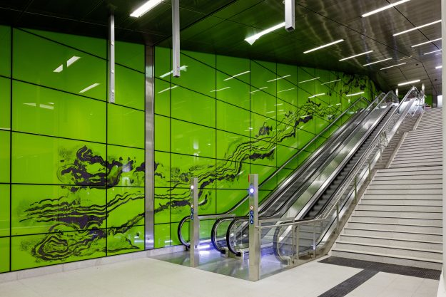 Graf Adolf Platz station features hundreds of panels of luminous green glass to create an immersive chromatic environment interrupted only by a powerful flow of lines that accompany the passenger from the street, through the concourse and down to the platform.