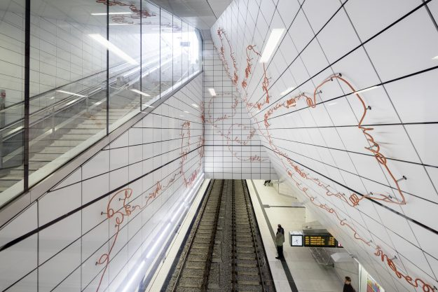 For Kirchplatz Station, Enne Haehnle wrote poetic texts and then gave them sculptural life. The lines of text leading passengers down into the subway begin at the three entrances, lead down into the station, intersect there and then accompany the passengers to the tracks.