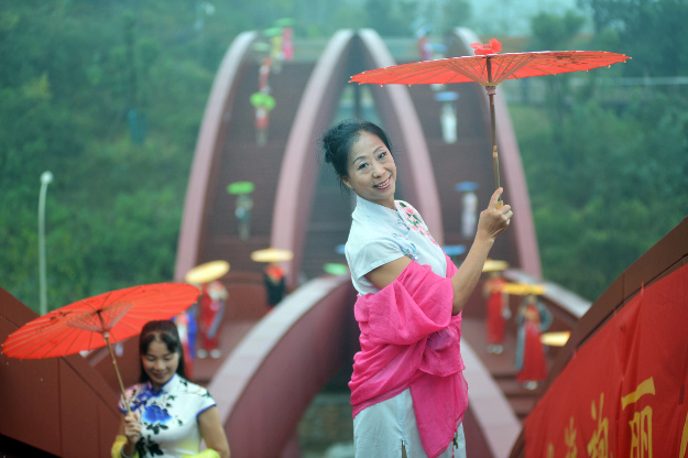 Aerial view of women displaying cheongsams on the knot-shaped pedestrian bridge in Changsha city.